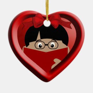 El aficionado a los libros del muchacho embroma el adorno de cerámica en forma de corazón