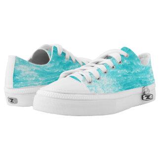 El agua de azules turquesas con salpica diseño zapatillas