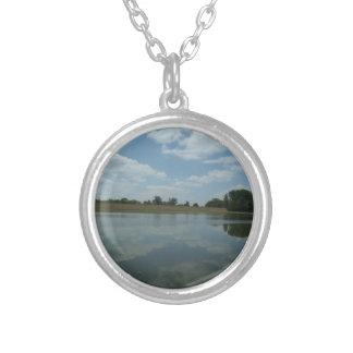 El agua del lago refleja las nubes blancas colgante redondo