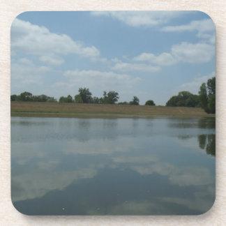 El agua del lago refleja las nubes blancas posavasos de bebida