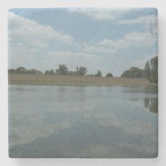 El agua del lago refleja las nubes blancas posavasos de piedra