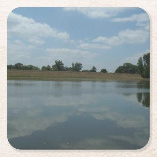 El agua del lago refleja las nubes blancas posavasos desechable cuadrado