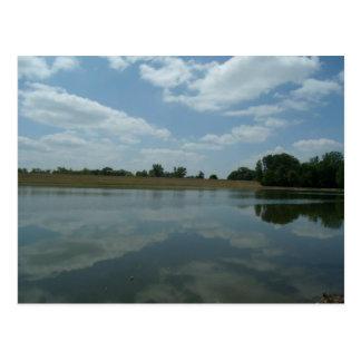 El agua del lago refleja las nubes blancas postales
