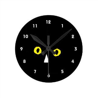 el amarillo negro principal del gato observa el di reloj redondo mediano