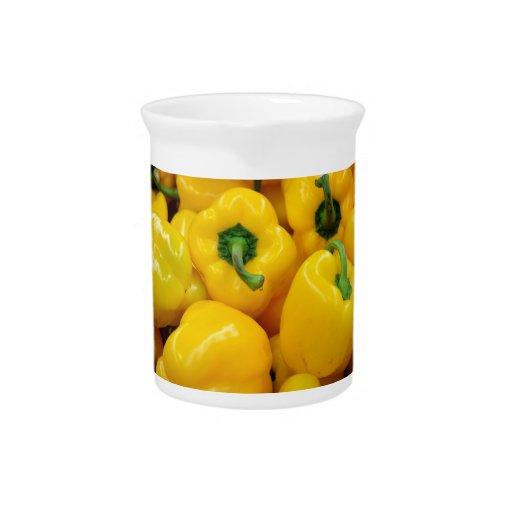 El amarillo sazona el fondo con pimienta jarras para bebida