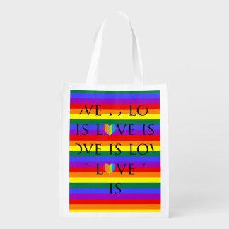 El amor colorido es amor en fondo del arco iris bolsas para la compra