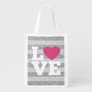 El amor con un corazón rosado brillante y la plata bolsas de la compra