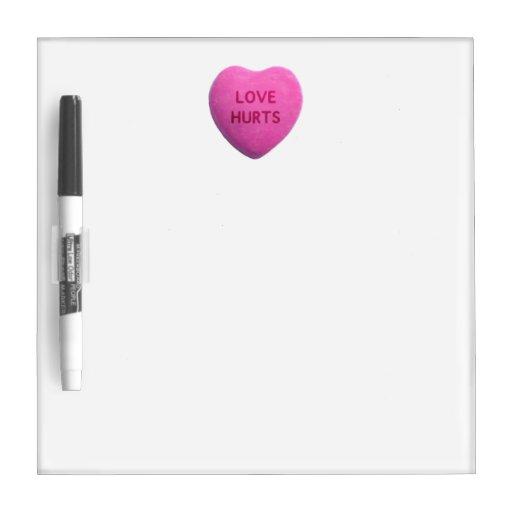 El amor daña el corazón rosado del caramelo pizarras