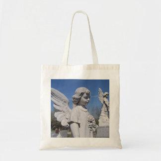 El ángel de los niños con el bolso de la lona del bolsas