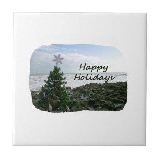 El árbol de navidad contra la playa oscila buenas  azulejos