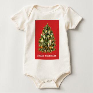 El árbol de navidad iluminado por velas adorna la mamelucos de bebé