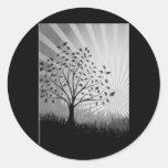 El árbol sale de la silueta y del resplandor solar pegatina redonda