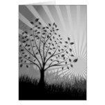 El árbol sale de la silueta y del resplandor solar tarjeta