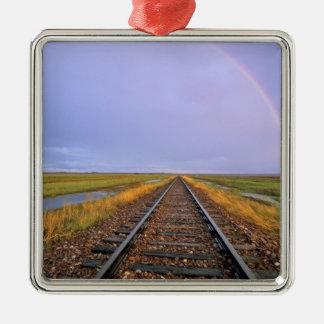 El arco iris sobre pistas de ferrocarril acerca a adorno navideño cuadrado de metal