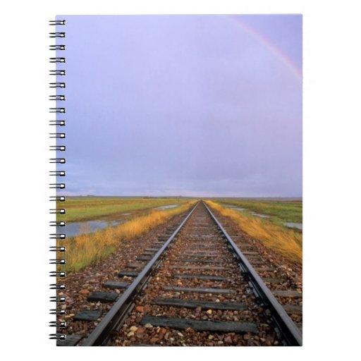 El arco iris sobre pistas de ferrocarril acerca a  libro de apuntes con espiral