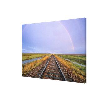 El arco iris sobre pistas de ferrocarril acerca a  impresion en lona