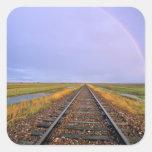 El arco iris sobre pistas de ferrocarril acerca a pegatina cuadrada