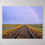 El arco iris sobre pistas de ferrocarril acerca a  póster