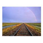 El arco iris sobre pistas de ferrocarril acerca a tarjeta postal