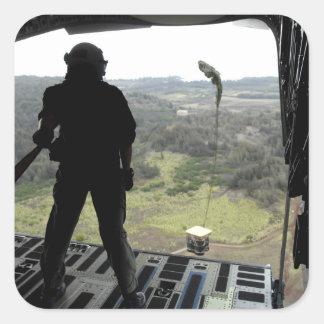 El aviador mira un paquete de la práctica caer pegatina cuadrada