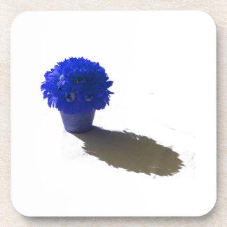El azul florece el cubo y la sombra blancos posavasos