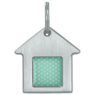 El blanco ancla el modelo verde del fondo del placas de nombre de mascota