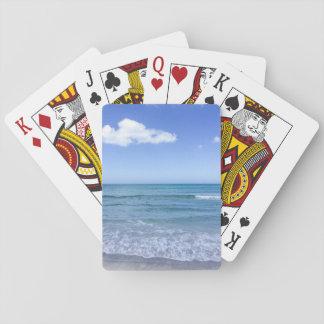 El blanco del cielo azul del agua de la playa se barajas de cartas