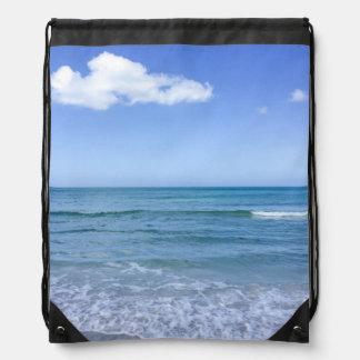 El blanco del cielo azul del agua de la playa se mochila