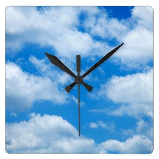 El blanco del cielo azul se nubla el fondo divino reloj cuadrado