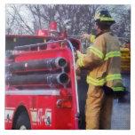 El bombero encendido apoya del coche de bomberos teja cerámica