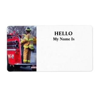 El bombero encendido apoya del coche de bomberos etiquetas de envío