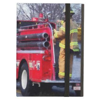 El bombero encendido apoya del coche de bomberos