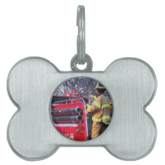 El bombero encendido apoya del coche de bomberos placa mascota
