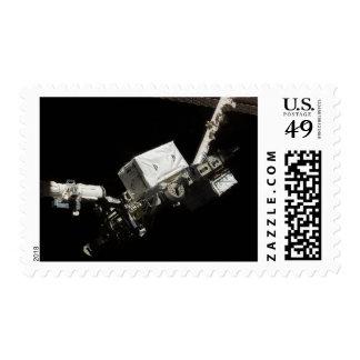 El brazo robótico del sistema de manipulante timbres postales