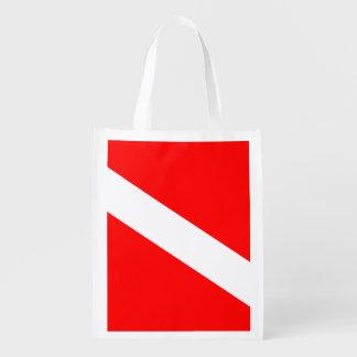 El buceador abajo señala por medio de una bandera bolsa reutilizable