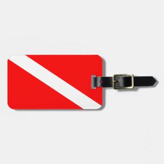 El buceador abajo señala por medio de una bandera etiquetas de maletas