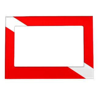 El buceador abajo señala por medio de una bandera marcos magneticos de fotos