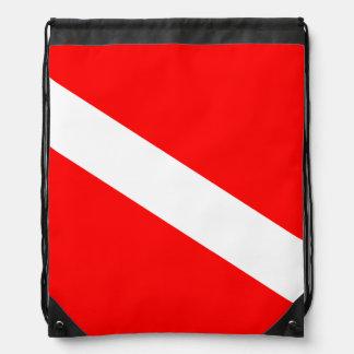 El buceador abajo señala por medio de una bandera mochilas
