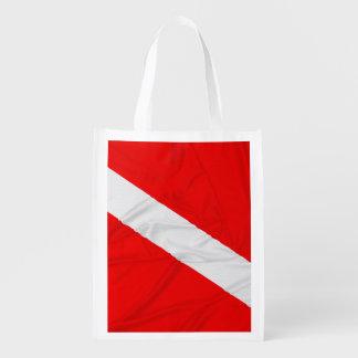 El buceador arrugado abajo señala por medio de una bolsa para la compra