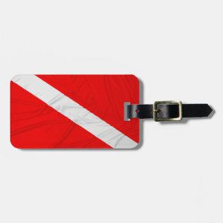 El buceador arrugado abajo señala por medio de una etiqueta para equipaje