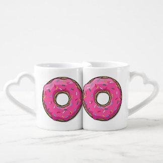 El buñuelo rosado del dibujo animado con asperja tazas para parejas