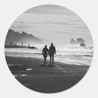 El caminar de común acuerdo en la playa pegatina redonda
