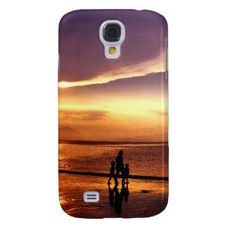 El caminar en la playa en la puesta del sol