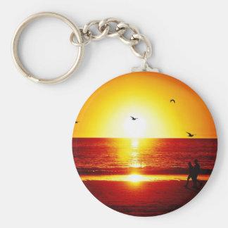 El caminar en la playa en la puesta del sol con el llavero
