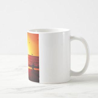 El caminar en la playa en la puesta del sol con el tazas de café