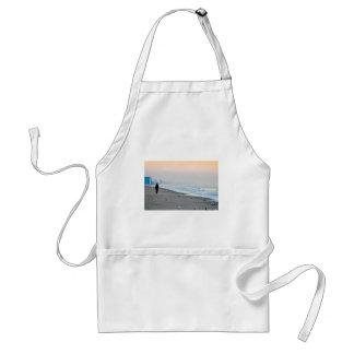 El caminar en la playa en la puesta del sol delantal