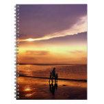 El caminar en la playa en la puesta del sol libreta