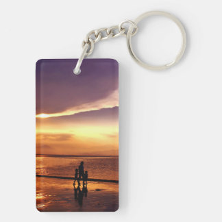 El caminar en la playa en la puesta del sol llaveros