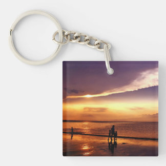 El caminar en la playa en la puesta del sol llavero