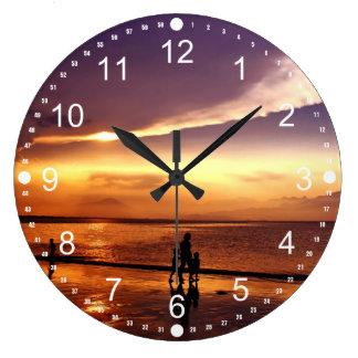 El caminar en la playa en la puesta del sol relojes